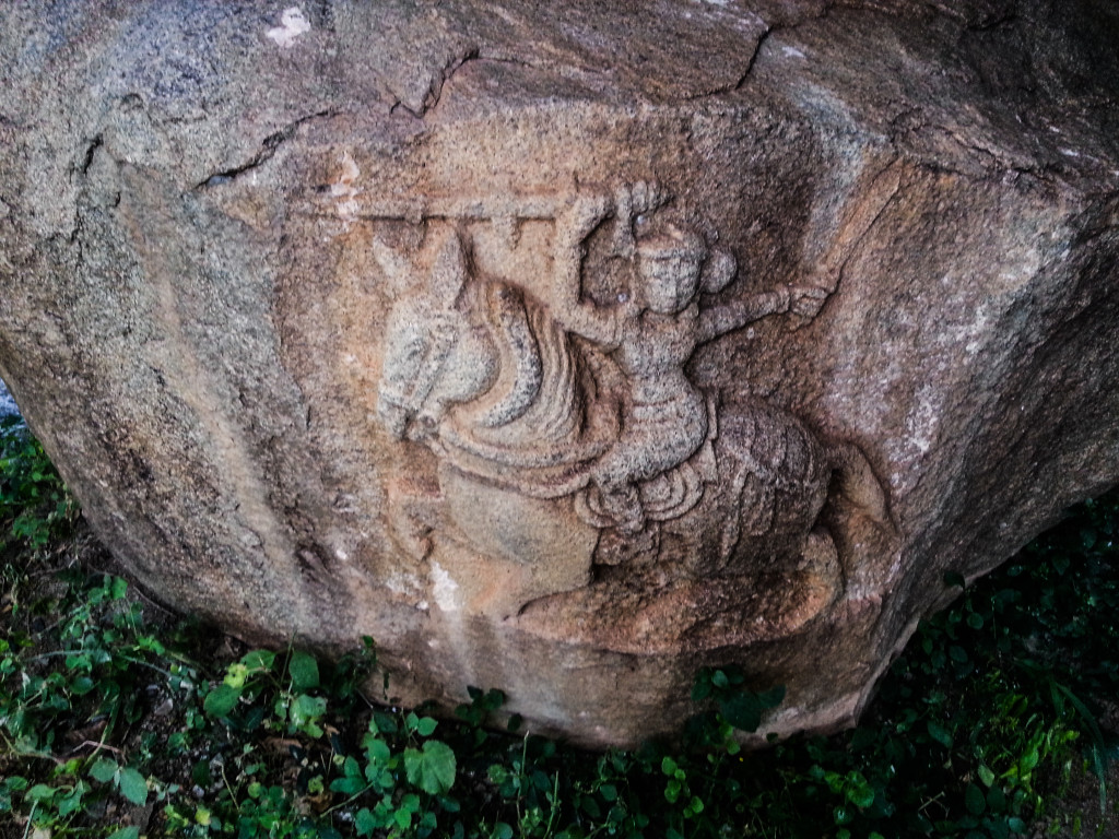 Rock relief sculpture on a boulder wall at entrance of the cave