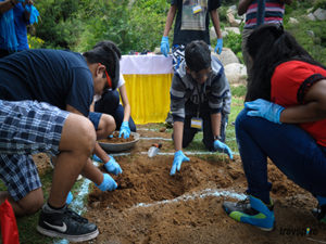 participants digging for artifacts on the mock excavation